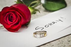 Sorry, broken engagement. Concept of a lost relationship with a letter, a red rose and an engagement ring left on a table Royalty Free Stock Images