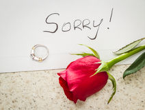 Sorry, broken engagement. Concept of a lost relationship with a letter, a red rose and an engagement ring left on a table royalty free stock photography