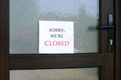 Sorry, We Are Closed. SORRY, WE'RE CLOSED sign on the front door of a little store Royalty Free Stock Image