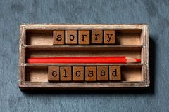 Sorry we are closed concept. Vintage box, wooden cubes phrase with old style letters, red pencil. Gray stone textured royalty free stock images