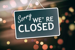 Sorry we are closed sign on abstract background. Sorry we are closed sign hanging on a glass storefront royalty free stock photos