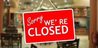 Sorry we are closed sign on glass storefront. Sorry we are closed sign hanging on a glass storefront Royalty Free Stock Image