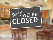 Sorry we are closed sign on glass storefront. Sorry we are closed sign hanging on a glass storefront Royalty Free Stock Images
