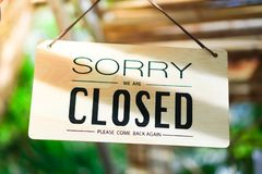 Sorry we are closed sign hang on door of business. A Sign board of sorry we are closed hang on door of business shop with nature green background stock image