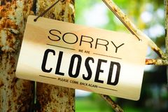 Sorry we are closed sign hang on door. A Sign board of sorry we are closed hang on door of business shop with nature green background royalty free stock photo