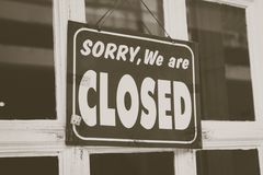 Sorry we are closed sign hang on door of business shop. A Sign board of sorry we are closed hang on door of business shop with nature green background royalty free stock photo