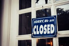 Sorry we are closed sign hang on door of business shop. A Sign board of sorry we are closed hang on door of business shop with nature green background stock photography