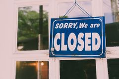 Sorry we are closed sign hang on door of business shop. A Sign board of sorry we are closed hang on door of business shop with nature green background royalty free stock photography