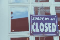 Sorry we are closed sign hang on door of business shop. A Sign board of sorry we are closed hang on door of business shop with nature green background stock image