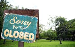 Sorry we are closed sign hanging outside at green grass field in. Big city park Stock Photos