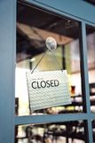 Sorry we are closed sign hanging on the window blue door shop Stock Images