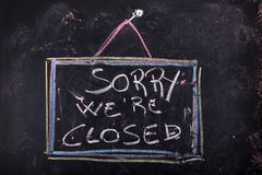 Sorry we are closed. Sign indicating the closing of a shop written with chalk on blackboard Royalty Free Stock Images