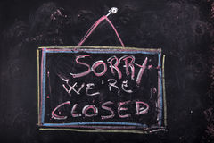Sorry we are closed. Sign indicating the closing of a shop written with chalk on blackboard Stock Images