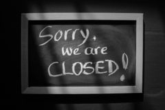 Sorry we are closed written on a board stock photography