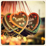Sorry gingerbread. Retro effect image of Gingerbread hearts hanging in a German Christmas market. The prominent heart is iced with the word Sorry. Cross stock photography