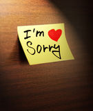 Sorry handwritten. On yellow note paper stock photos