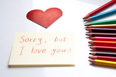 Sorry, but I love you. Colorful pencils, red heart shaped card and love notes on white background Royalty Free Stock Photography