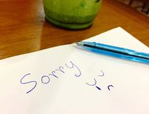 Sorry letter. Hand writing by pen with cartoon emotions sad and crying on white paper on the wood table stock image