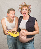 Sorry Man with Angry Expecting Woman. Sorry hillbilly men giving pregnant women candy Royalty Free Stock Photo