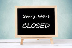 Sorry, we& x27;re close on blackboard over green wall background. Sorry, we& x27;re close on blackboard over green wall background, business hours sign Stock Photos