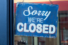 Sorry We're Closed Sign. Worn blue sign with the words Sorry We're Closed hanging from chains outside a shop Stock Images