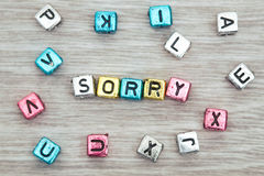 Sorry sign. SORRY cube blocks arranged on gray wooden background royalty free stock photography
