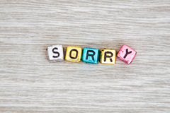 Sorry sign. SORRY cube blocks arranged on gray wooden background stock images