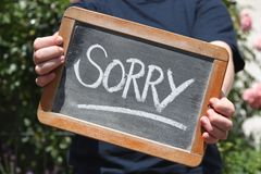 SORRY. Written with chalk on slate shown by young female Royalty Free Stock Image