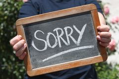 Sorry. Written with chalk on writing slate shown by young female stock photos