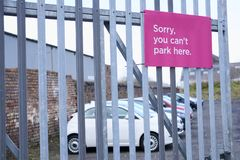 Sorry you can`t park here sign on entrance office fence of car park. With cars in background blurred Royalty Free Stock Photo