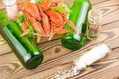 Sort d'écrevisses rouges bouillies et aneth frais vert dans la cuvette en céramique blanche près de deux pleines bouteilles de bi image libre de droits