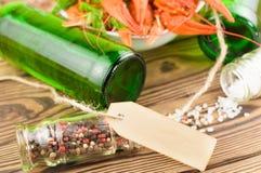 Sort d'écrevisses rouges bouillies et aneth frais vert dans la cuvette en céramique blanche près de deux pleines bouteilles de bi photos libres de droits