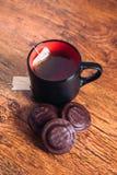 Sort de gâteaux aux pépites de chocolat et d'un thé de tasse sur le fond en bois photos libres de droits