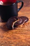 Sort de gâteaux aux pépites de chocolat et d'un thé de tasse sur le fond en bois Photos stock