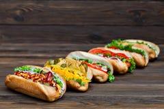 Sort de grands hot-dogs délicieux avec de la sauce et des légumes sur le fond en bois Photos stock