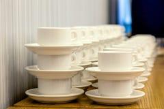 Sort de paires blanches de thé de porcelaine dans les piles dans une ligne droite Co image stock