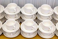 Sort de paires blanches de thé de porcelaine dans les piles dans une ligne droite Co images stock