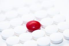 Pilules blanches avec une pilule rouge Images libres de droits