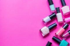Sort de vernis à ongles de bouteilles sur la vue supérieure de fond rose photographie stock