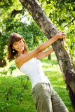 Sort of flight. Portrait of a girl clinging to a tree. Kolomenskoe, Moscow royalty free stock photo