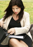 Sort it out. Woman sorting through her bag Royalty Free Stock Photo