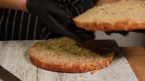 Sortant les gâteaux de Savoie prêts à l'emploi du four, les coupant dans la couche de gâteau pour faire un gâteau d'écrou-banane clips vidéos