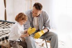 Sorte drôle aidant son papa à mettre dessus des gants Photo libre de droits