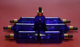 Sorted blue glass bottles with a golden dropper on a red background.  royalty free stock photography