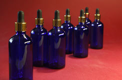 Sorted blue glass bottles with a golden dropper on a red background.  Stock Photography