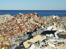 Sorted Building Rubble. Concrete rubble from buildings is sorted into piles along the shore line stock photo