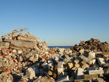 Sorted Building Rubble. Concrete rubble from buildings is sorted into piles along the shore line royalty free stock photography