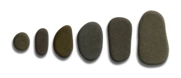Sorted flat pebbles. A row of flat pebble stones in light back Stock Photography