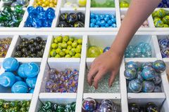 A child& x27;s hand picking up marbles royalty free stock photos