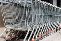Sorted metal shopping carts. Many carts one behind the other outside a mall Stock Image